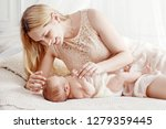 mother and child on a white bed.... | Shutterstock . vector #1279359445