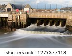 Long expsure of a waterfall flowing into West Bay harbour from the river Brit in Dorset