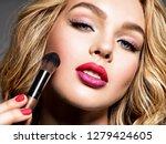beautiful woman applying makeup....   Shutterstock . vector #1279424605