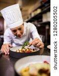 female chef garnishing... | Shutterstock . vector #1280205502