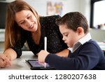 Small photo of Close up of young female teacher sitting at desk with a Down syndrome schoolboy using a tablet computer in a primary school classroom, smiling, close up, side view