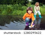 two boy play in puddle summer... | Shutterstock . vector #1280295622