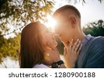 young loving couple are looking at each other tenderly and hugging at sunset near the river, photo to the day of Saint Valentine