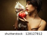 Portrait of two friends:  fashionable model with sexy red lips holding red heart (love symbol) and little white chinese crested dog. Both posing over golden background. Profile. Close up. Copy-space. - stock photo