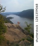 Small photo of Cold Spring, NY, USA July 12, 2015 A young man pulls himself over a rock ledge along Breakneck Ridge in Cold Spring, New York