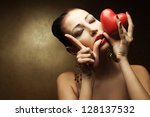 """Portrait of a fashionable model with sexy red lips holding red heart (love symbol) and showing """"L"""" (love symbol) with her hand over golden background. Close up. Copy-space. Studio shot - stock photo"""