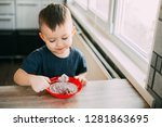 a child in the kitchen eating... | Shutterstock . vector #1281863695