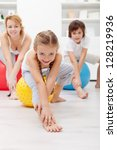 Gymnastic at home - woman and kids using large exercise balls - stock photo