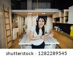 cheerful woman listening to... | Shutterstock . vector #1282289545