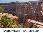hiker is sitting on the cliff... | Shutterstock . vector #1282301605