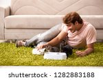 Stock photo young man playing with kitten at home 1282883188