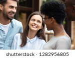 Small photo of Pretty diverse girls and guys best friends standing outdoor talking joking laughing feels good and happy. Friendship between multiracial young people warm relations amity and racial tolerance concept