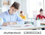 serious schoolboy with pencil... | Shutterstock . vector #1283022262