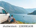 young man sitting near suv car...   Shutterstock . vector #1283081638