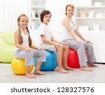 Kids exercising with their mother using large gymnastic balls - stock photo