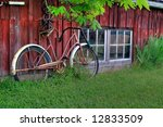 Rusty Bicycle Against Red Barn
