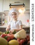 little girl cuts fruit in... | Shutterstock . vector #1283452618