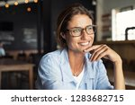 Stock photo portrait of beautiful mature woman sitting in cafeteria looking away cheerful mature woman wearing 1283682715