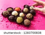 Stock photo st valentine s day heart shape made of chocolate candies on a pink background women s hand takes 1283700838