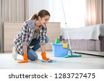 young woman washing floor with... | Shutterstock . vector #1283727475