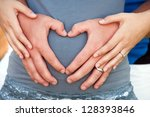 Close up of couple's hands making heart symbol on pregnant tummy. - stock photo