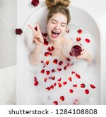 Stock photo relaxing woman smiling in hot bath with bubbles beautiful woman in bath with rose petals drinking 1284108808