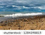 tiny waves crashing on pebble... | Shutterstock . vector #1284398815
