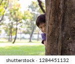 handsome boy hiding behind tree ... | Shutterstock . vector #1284451132
