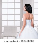 Beautiful brunette young woman in wedding dress, portrait in profile, indoors - stock photo