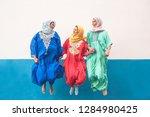 happy muslim women jumping... | Shutterstock . vector #1284980425