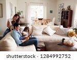 young hispanic family sitting... | Shutterstock . vector #1284992752