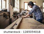 Skilled carpenter wearing safety gear sawing a piece of wood with a mitre saw while working alone in his woodworking studio - stock photo