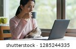 Stock photo woman work on computer with her cat at home 1285244335