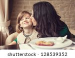 mom and young daughter eating... | Shutterstock . vector #128539352