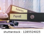 Small photo of Payroll and salaries folders stack with label on black binder on paperwork documents summary report, HR-human resources business and bookkeeping accountancy concept in busy offices