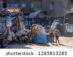 Small photo of 11/18/2018 Cairo, Egypt, children go to school on the street of a garbage town among a bunch of garbage and unacceptable stench on a sunny day