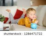 little boy looks on moneybox... | Shutterstock . vector #1286471722
