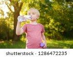 little boy drinking water... | Shutterstock . vector #1286472235