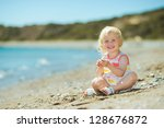 happy baby girl playing on beach | Shutterstock . vector #128676872