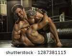 Small photo of Two MMA fighters grappling on training in gym. Muscular sportsman with aggressive look looking at camera, sitting on chest of rival and choking him with hand, opponent lying in floor and resisting.