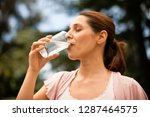 Small photo of Twenty something woman drinks a glass of water.
