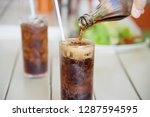 hand pour soft drink into a... | Shutterstock . vector #1287594595