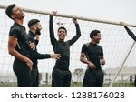 Soccer players standing near the goalpost relaxing and laughing. Footballers taking a break during a football match talking and laughing.