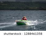 boy being towed on an... | Shutterstock . vector #1288461358