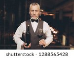 experienced sommelier in bow... | Shutterstock . vector #1288565428
