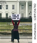 "Small photo of WASHINGTON, DC - JANUARY 19, 2019: Women's March 2019, woman protester stands in front of the White House holding sign, ""Rise Up America Rise Up"""