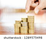 hand stacking coin on desk ... | Shutterstock . vector #1289575498