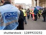 Small photo of London, UK. 12th January 2019. Police Liaison Officer sign on the back of a blue reflective jacket worn by police officers escorting & monitoring a street demonstration through central London, UK.