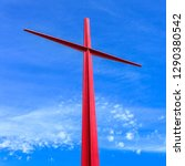 Small photo of Large red christian cross on sky background. Passion symbology. Easter.
