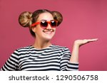 Stock photo hipster young positive girl in sunglasses with funny hairstyle showing product with open hand palm 1290506758